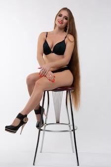 Uma jovem loira de biquíni está sentada em uma cadeira.