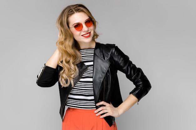 Uma jovem loira de óculos vermelhos colocou um braço atrás da cabeça, a outra na cintura
