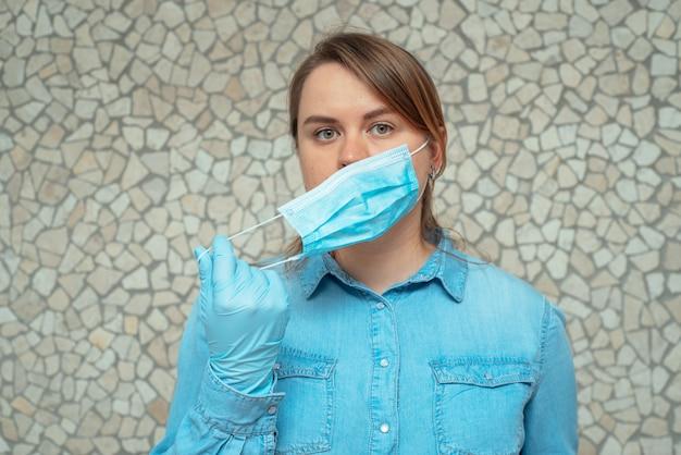 Uma jovem loira em luvas de proteção azuis coloca uma máscara protetora no rosto