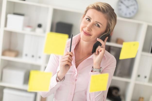 Uma jovem loira está de pé no escritório ao lado de uma placa transparente com adesivos