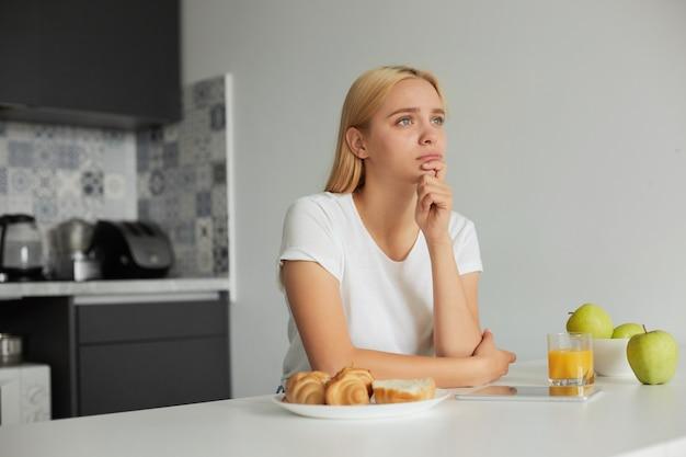 Uma jovem loira está sentada à mesa da cozinha, triste, olhando pensativamente para o lado da janela