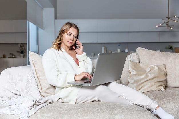 Uma jovem loira está sentada em um sofá com um laptop e um telefone em uma grande sala de estar bem iluminada. trabalho remoto e educação a distância.