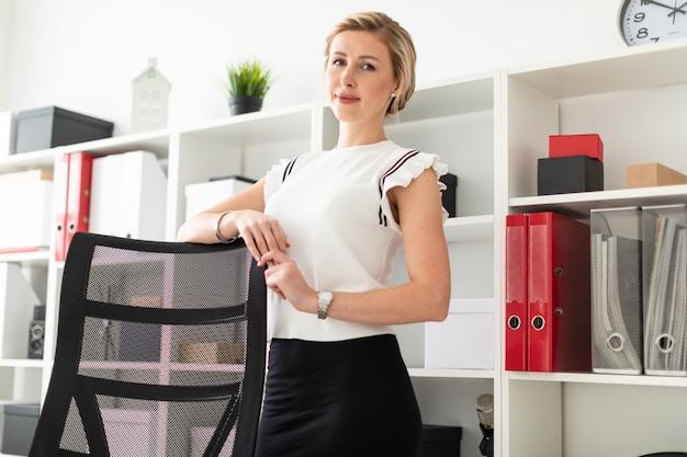 Uma jovem loira fica no escritório ao lado das prateleiras com documentos