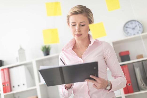 Uma jovem loira fica no escritório ao lado de uma placa transparente com adesivos e detém documentos e um lápis nas mãos dela.