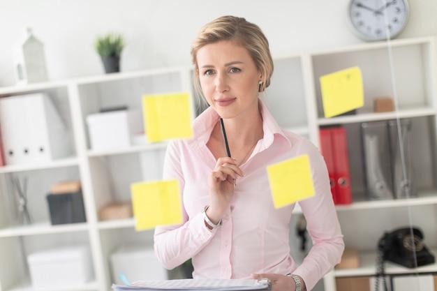 Uma jovem loira fica no escritório ao lado de uma placa transparente com adesivos e mantém documentos