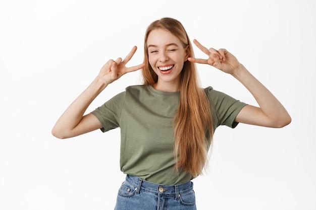 Uma jovem loira positiva e feliz, piscando e sorrindo com os dentes brancos, mostrando o gesto do sinal v da paz perto dos olhos, em pé alegre contra a parede branca