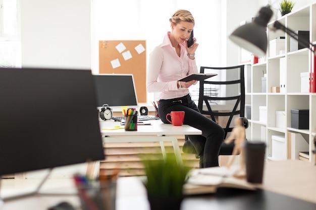 Uma jovem loira se agachou na mesa do escritório, falando ao telefone e segurando um caderno na mão.