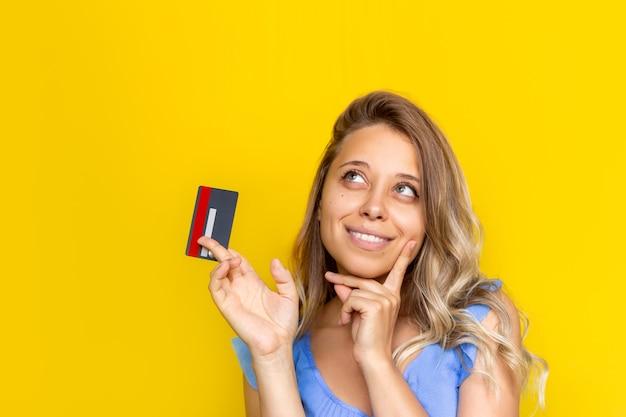 Uma jovem loira segurando um cartão de crédito de plástico na mão e pensando em como gastar o dinheiro