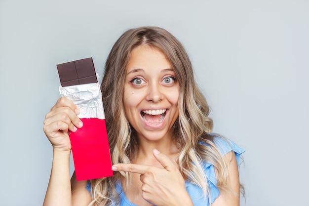 Uma jovem loira sorridente aponta para um chocolate amargo escuro em um pacote vermelho com espaço vazio na cópia