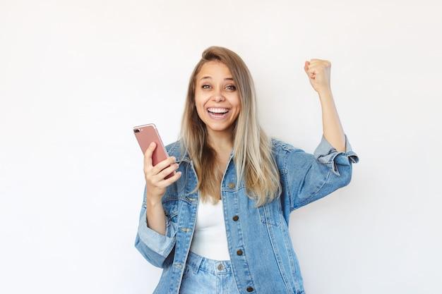 Uma jovem loira sorridente e animada fica feliz por ganhar na loteria ou por descobrir boas notícias