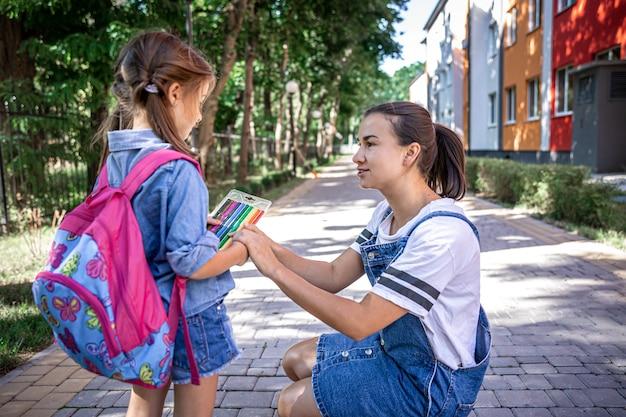 Uma jovem mãe acompanha a filha à escola e dá-lhes marcadores coloridos.