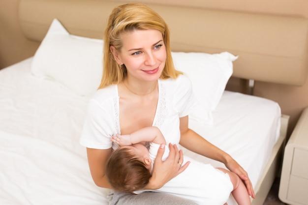 Uma jovem mãe amamentando sua filhinha enquanto a segura em seus braços