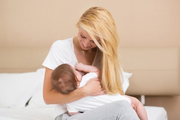 Uma jovem mãe amamentando sua filhinha enquanto segura em seus braços em um quarto doméstico espaçoso e iluminado