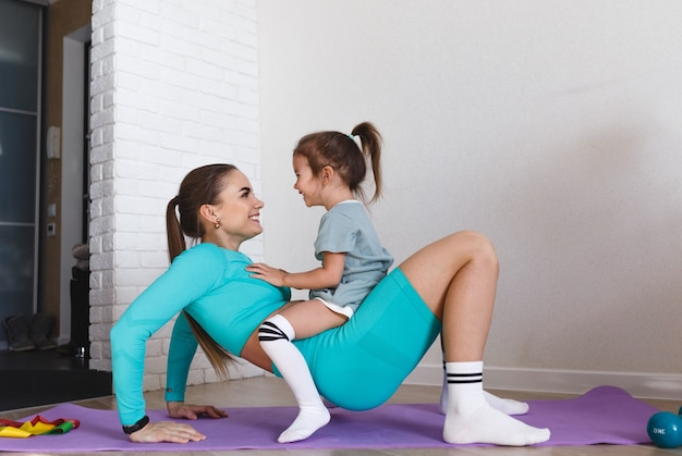Uma jovem mãe atlética e uma menina fazem exercícios juntas em casa