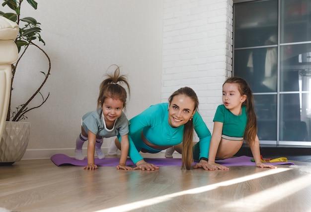 Uma jovem mãe atlética em um agasalho está envolvida em exercícios físicos em casa com suas filhas