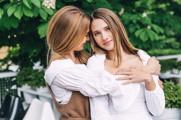 Uma jovem mãe beija e abraça sua linda filha