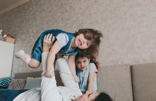Uma jovem mãe brinca com as filhas deitadas no sofá, levantando uma menina nos braços estendidos. jogos de familia