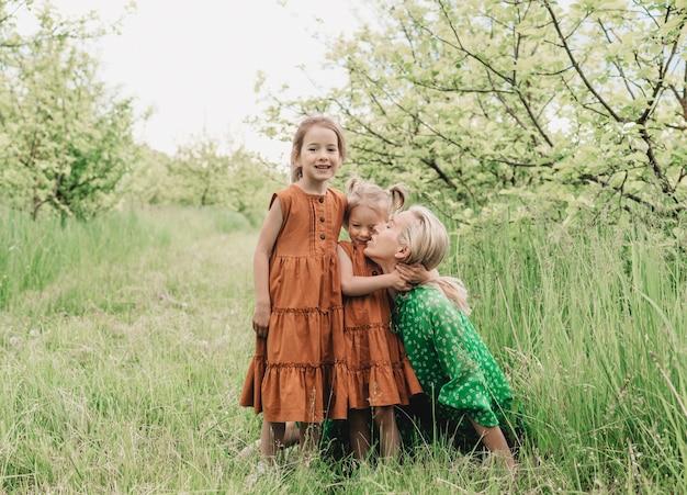 Uma jovem mãe brinca com duas filhas no jardim de primavera. crianças felizes e mãe