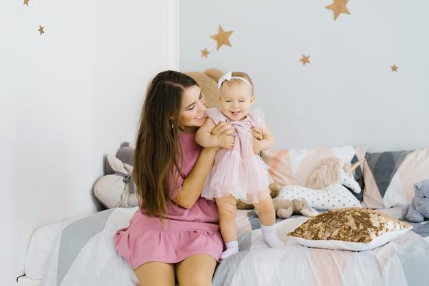 Uma jovem mãe brinca com sua filha de um ano, sentada na cama do quarto das crianças.