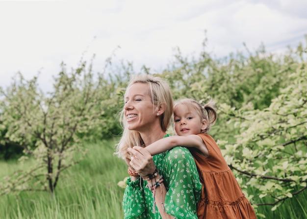 Uma jovem mãe brinca com sua filha rolando-a de costas no meio de um jardim verdejante. jogos de família conjuntos