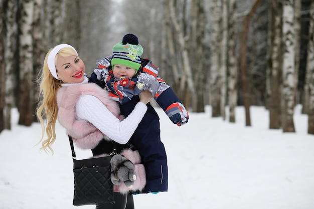 Uma jovem mãe caminha em um dia de inverno com um bebê nos braços no parque