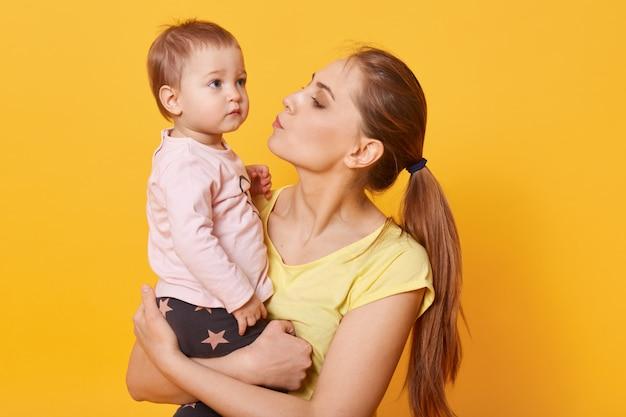 Uma jovem mãe carinhosa tenta acalmar a filha que chora.