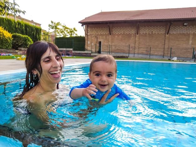 Uma jovem mãe caucasiana com seu bebê curtindo o verão nadando pela primeira vez em uma piscina