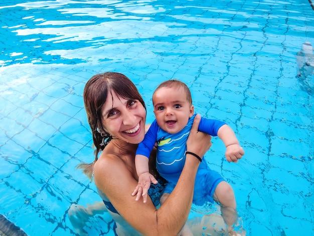 Uma jovem mãe caucasiana com seu bebê curtindo o verão tomando banho pela primeira vez em uma piscina