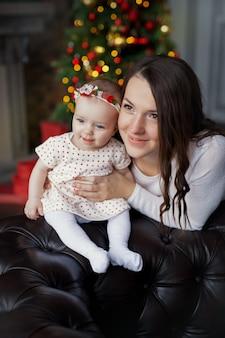 Uma jovem mãe com a filha na árvore de natal.