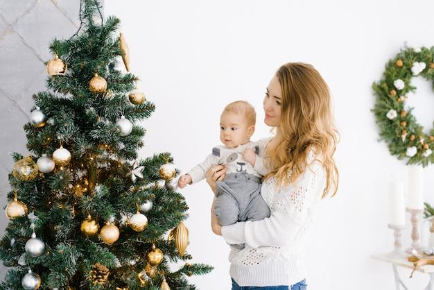 Uma jovem mãe com cabelo loiro segura o filho pequeno nos braços, eles comemoram alegremente o natal e o ano novo