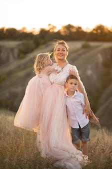 Uma jovem mãe com filhos entra em um campo ao pôr do sol.