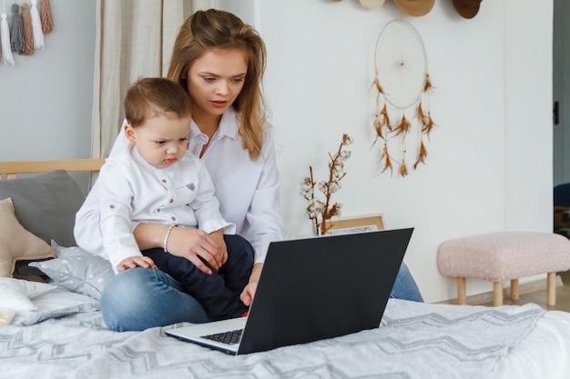Uma jovem mãe com seu filho amado no quarto na cama com um laptop. trabalhe em casa com um conceito infantil