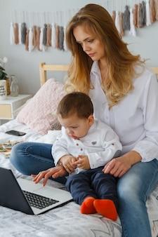 Uma jovem mãe com seu filho amado no quarto na cama com um laptop
