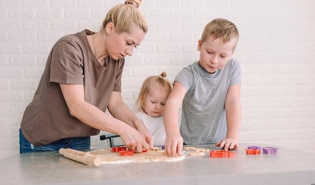 Uma jovem mãe com seu filho e filha juntos preparam biscoitos na cozinha. família feliz cozinhando junta