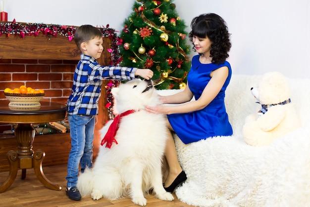 Uma jovem mãe com seu filho e um cachorro em uma árvore de natal.