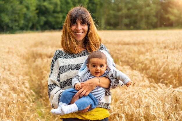 Uma jovem mãe com seu filho em um campo de palha amarela na bretanha francesa no verão de julho, perto da floresta de broceliande. frança