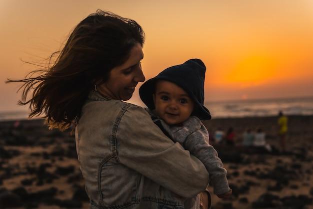Uma jovem mãe com seu filho no toston lighthouse sunset, punta ballena, perto da cidade de el cotillo, ilha de fuerteventura, ilhas canárias. espanha
