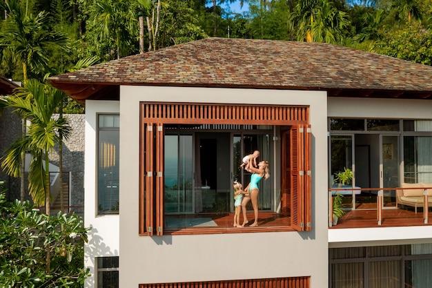 Uma jovem mãe com seus dois filhos está na varanda de uma villa tropical