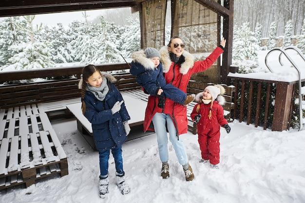Uma jovem mãe com seus filhos se divertindo no inverno