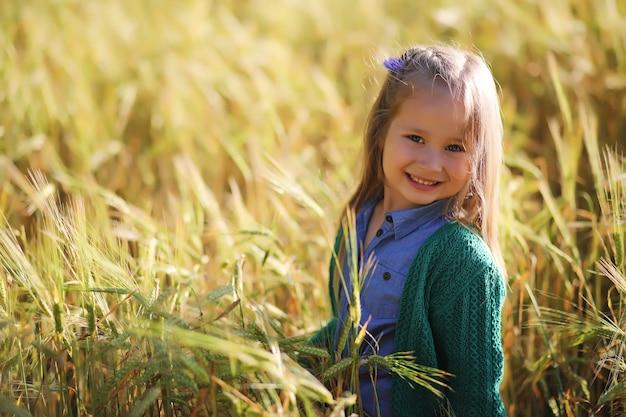 Uma jovem mãe com sua filha em um passeio em campos de trigo