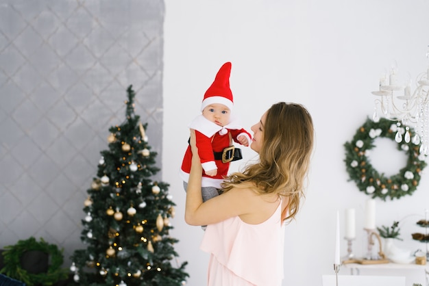 Uma jovem mãe com um bebê em uma fantasia de papai noel nos braços perto da árvore de natal na sala de estar em casa