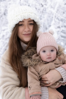 Uma jovem mãe com uma criança pequena brinca na neve, eles estão se divertindo e curtindo a queda de neve.