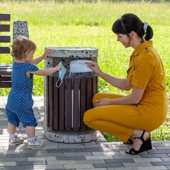 Uma jovem mãe com uma filha pequena joga máscaras médicas no lixo em um dia ensolarado de verão, o conceito de acabar com a pandemia do coronavírus