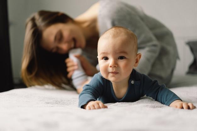 Uma jovem mãe é brincar com o menino. mãe de um bebê que está amamentando. feliz maternidade. a família está em casa retrato de uma feliz mãe e filho.