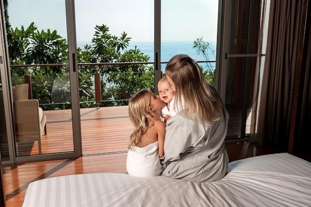 Uma jovem mãe e dois filhos estão sentados na cama e olhando pela janela