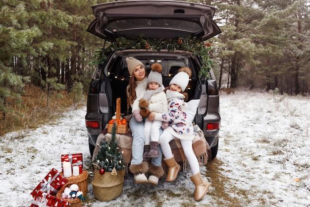 Uma jovem mãe e duas meninas estão sentadas no porta-malas de um carro