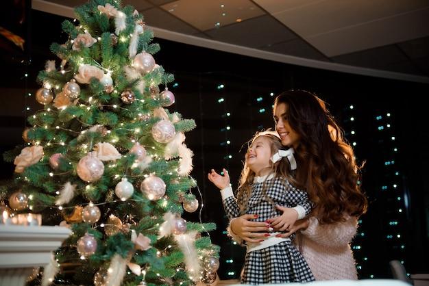 Uma jovem mãe e filha decoram a árvore de natal com bolas novas.