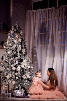 Uma jovem mãe e filha em vestidos combinando decoram a árvore de natal com bolas novas