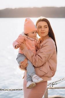 Uma jovem mãe elegante e sua filha passar algum tempo juntos no lago no parque