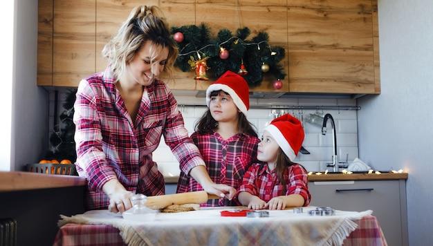 Uma jovem mãe ensina suas filhas na cozinha a fazer uma sobremesa deliciosa com massa.